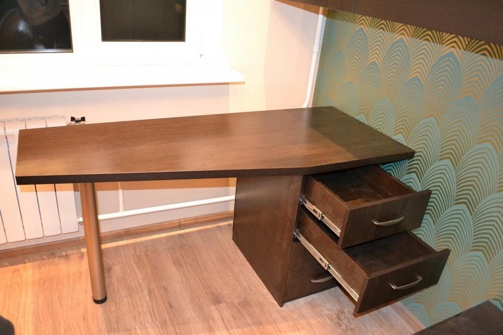 Письменный стол темного цвета.